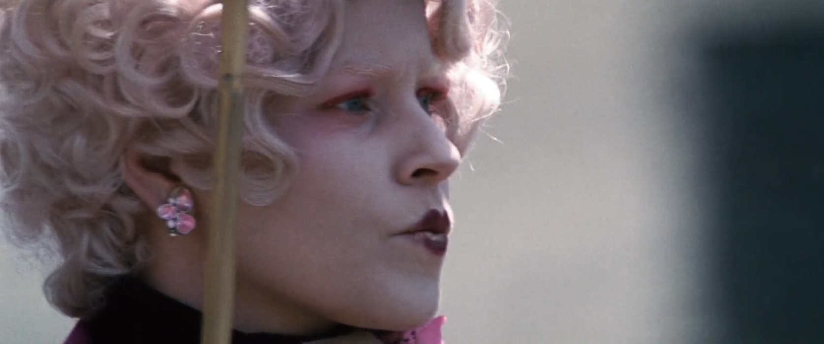 Elizabeth Banks as Effie Trinket light cotton candy pink curly hair