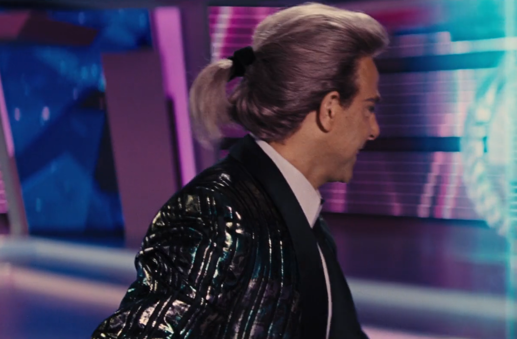 Stanley Tucci the hunger games putple pony tail hairstyle